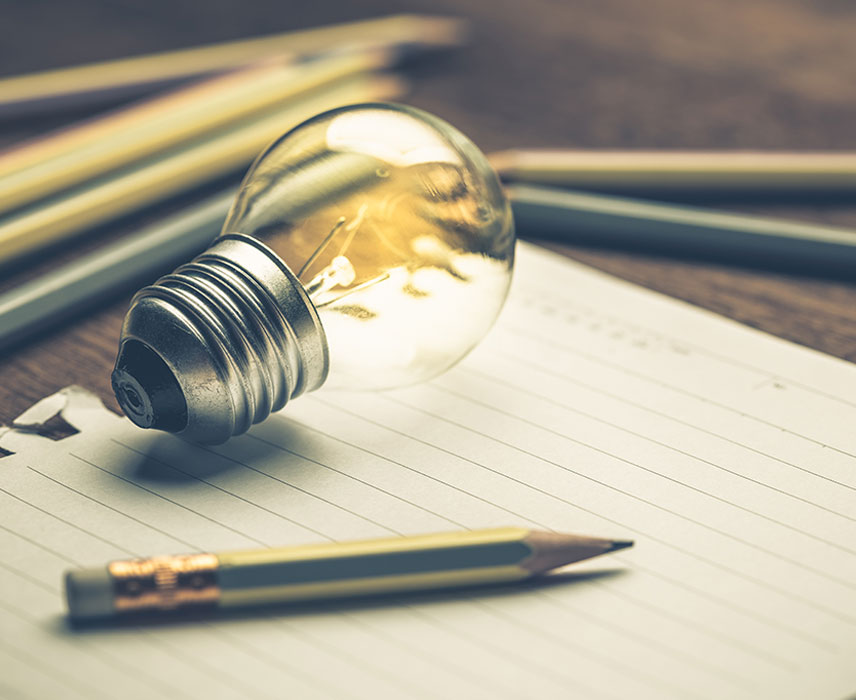 lightbulb and pencil resting on paper